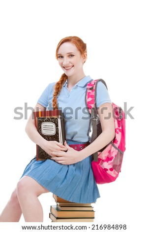 Young Caucasian female college student with backpack in skirt sitting on huge pile of educational books from library - stock photo