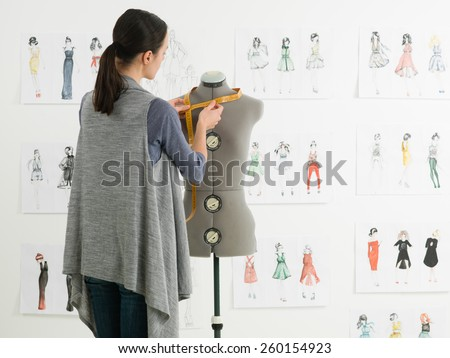 young caucasian female fashion designer taking measurements on mannequin in her studio