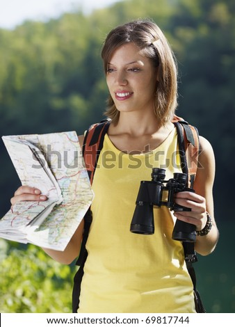 young caucasian female hiker reading map and holding binoculars. Vertical shape, waist up, front view