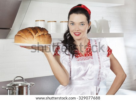 Young Caucasian female holding plate with baked bread in the kitchen - stock photo
