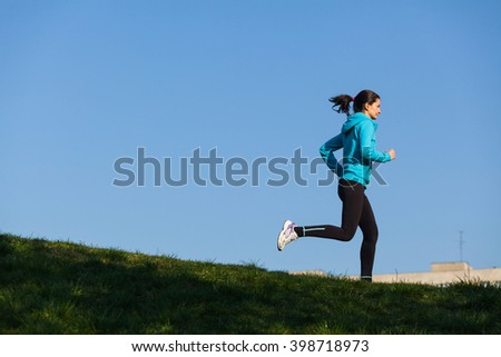 Young caucasian female is running on a green hill in a sunny afternoon