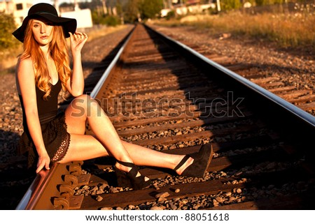 Young caucasian female model posing on railroad tracks with a large black hat.