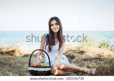 young caucasian female on seaside with basket with fruits. Girl eating fruits, healthy eating and healthy living concept - stock photo