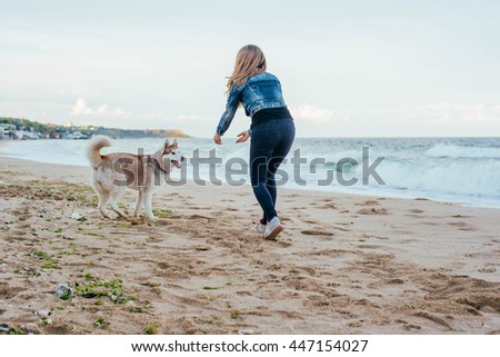 young caucasian female playing with siberian husky dog on beach