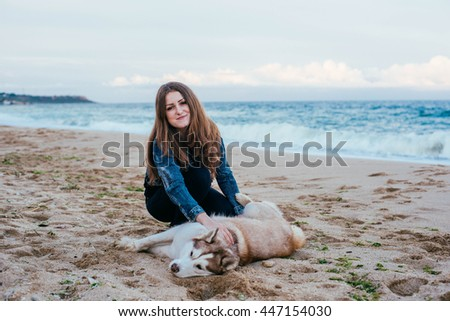 young caucasian female playing with siberian husky dog on beach - stock photo