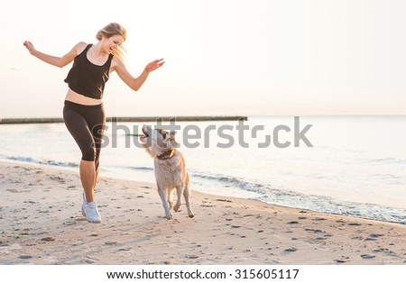young caucasian female playing with siberian husky dog on beach during sunrise