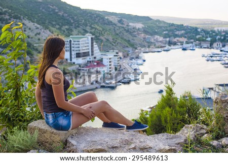 young caucasian female sitting on seaside looking at cityscape