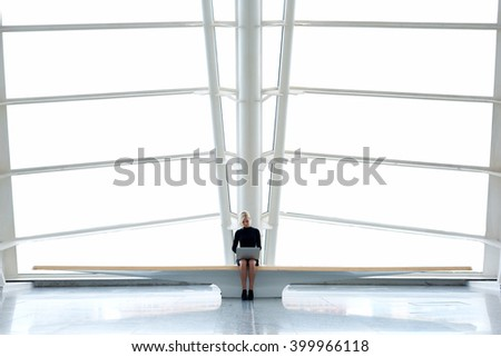 Young caucasian female student is using net-book or laptop computer for search needed information, while is sitting in modern university interior with contemporary design. Copy space for advertising - stock photo