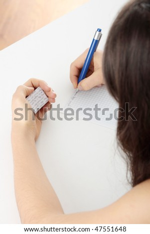 Young caucasian female student stands by school desk and  cheat - stock photo