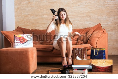 young caucasian female with shopping bags in living room.    - stock photo