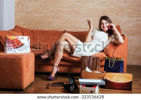 young caucasian female with shopping bags talking on mobile phone in living room.    - stock photo