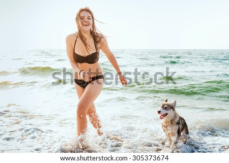 young caucasian female with siberian husky puppy playing on beach