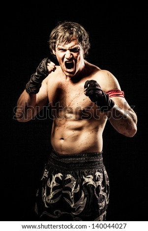 young caucasian fighter yelling with his fists ready to fight dressed in silk boxing shorts