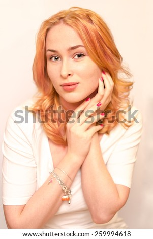 young caucasian ginger girl wearing white t-shirt with her arms near the face forward looking - stock photo