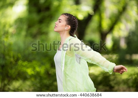 Young caucasian girl exercising in the park while listening to a music. - stock photo