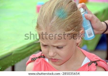 young Caucasian girl getting her blond hair spray painted - stock photo