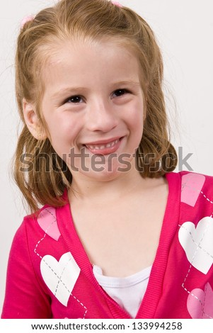 Young Caucasian girl in a heart sweater making funny face - stock photo