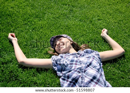 Young caucasian girl laying on the green grass
