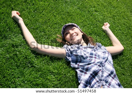 Young caucasian girl relaxing on the green grass
