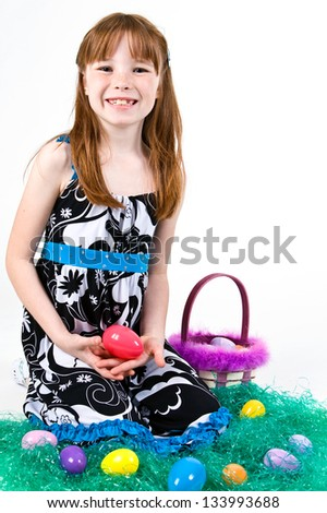 Young Caucasian girl sitting in grass with an Easter egg - stock photo