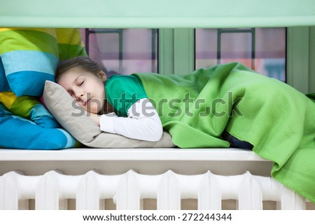 Young Caucasian girl sleeping on the plastic window sill over heating radiator - stock photo