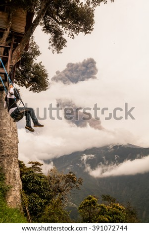 Young Caucasian Girl Taking A Ride On The Swing Located At Casa Del Arbol, The Tree House, Tungurahua Volcano Explosion March 2016 In The Background, Ecuador, South America  - stock photo