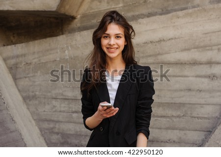 Young Caucasian Girl Text Messaging Looking At The Camera. - stock photo