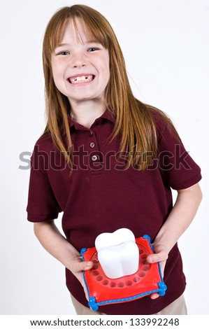 Young Caucasian girl waiting on the tooth fairy holding a large tooth shaped piggy bank with slots to hold baby teeth. - stock photo