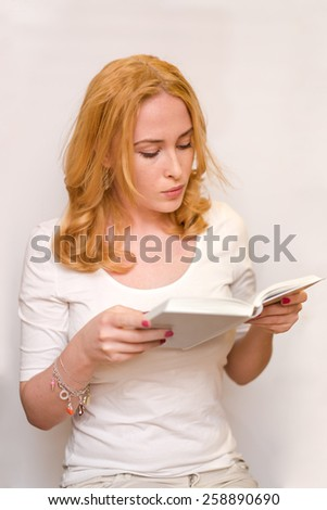 young caucasian girl wearing white t-shirt reading book isolated on a white background - stock photo