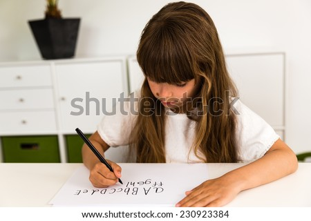 Young caucasian girl with long hair writing letters on a white piece of paper.