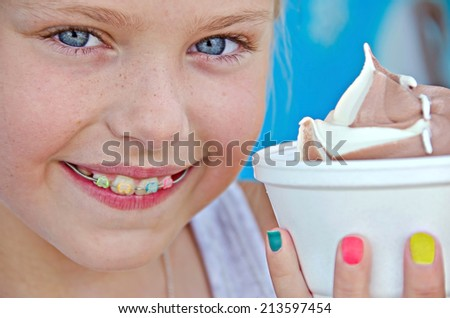 young Caucasian girl with orthodontic smile and ice cream in a styrofoam cup - stock photo