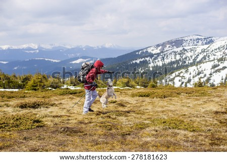 young caucasian guy hiking outdoors with a dog
