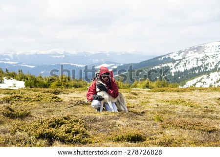 young caucasian guy hiking outdoors with a dog - stock photo
