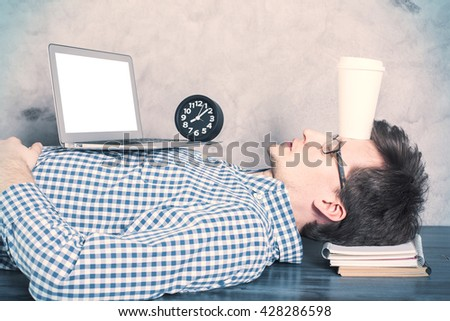 Young caucasian guy with blank white laptop screen sleeping on office desktop with coffee cup on forehead. Mock up - stock photo