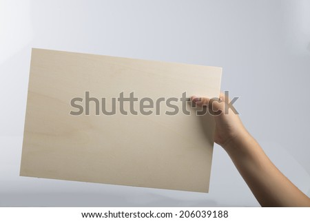 Young caucasian hand holding from right a light color plywood square blank signboard isolated on white background. There are no elements to distract viewer from reading any message written on the sign - stock photo