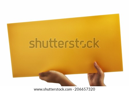 Young caucasian hands holding a deep yellow orange plywood square blank signboard isolated on white background. There are no elements to distract viewer from reading any  message on the sign - stock photo