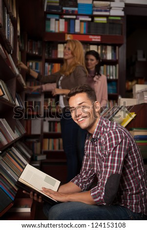 young caucasian handsome guy in a bookstore smiling with an opened book in his hands, with other people in background