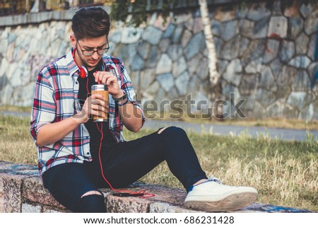 Young caucasian handsome hipster man relaxed at sunny day on the park