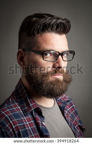 Young caucasian handsome hipster with beard posing in studio - stock photo