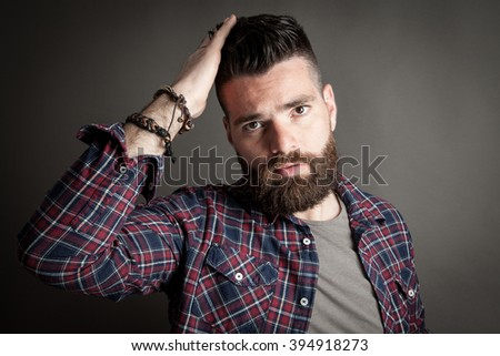 Young caucasian handsome hipster with beard posing in studio