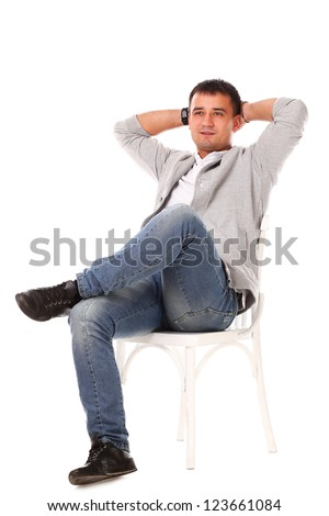 Young caucasian handsome man sitting on the chair isolated over white background