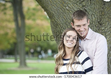 Young caucasian happy couple hugging in the park on a sunny day.