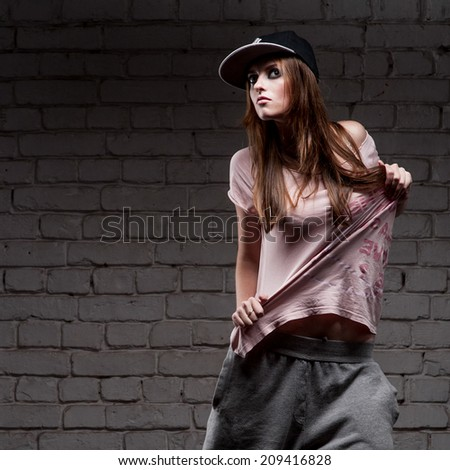 young caucasian hip-hop dancer girl showing some moves over brick wall background - stock photo