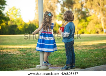 Young Caucasian kids looking on the field during the sunset on a summer day. Also available in vertical format.