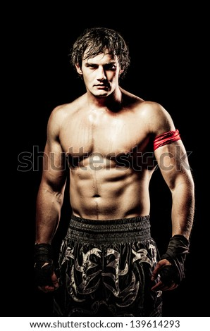 young caucasian male boxer wearing his black boxing shorts and gloves with a red bandage attached to his upper arm