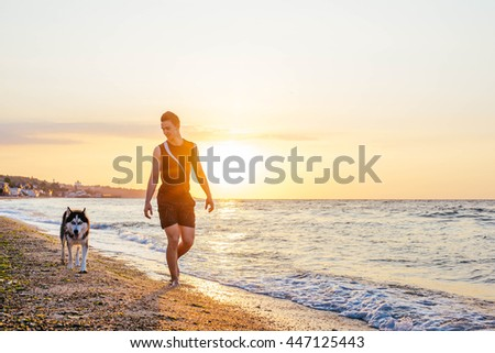 young caucasian male walking with siberian husky dog on beach