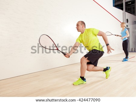 young caucasian man and woman playing squash. - stock photo