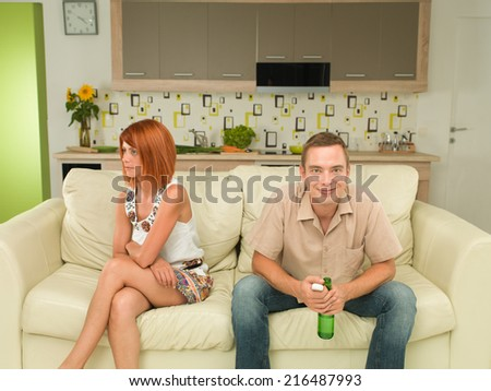 young caucasian man and woman sitting on couch watching television, the woman beeing upset
