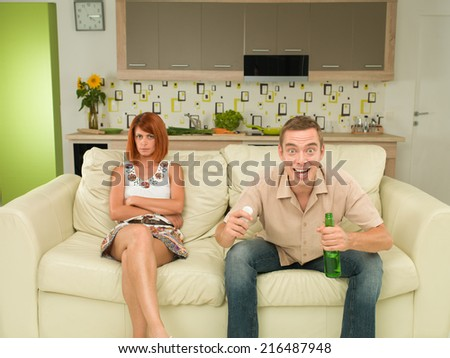 young caucasian man and woman sitting on couch watching tv together - stock photo