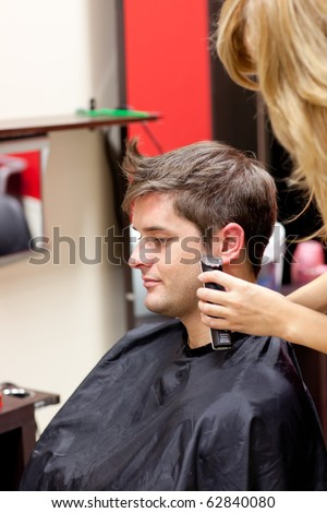 Young caucasian man being shaved in a hairdressing salon - stock photo
